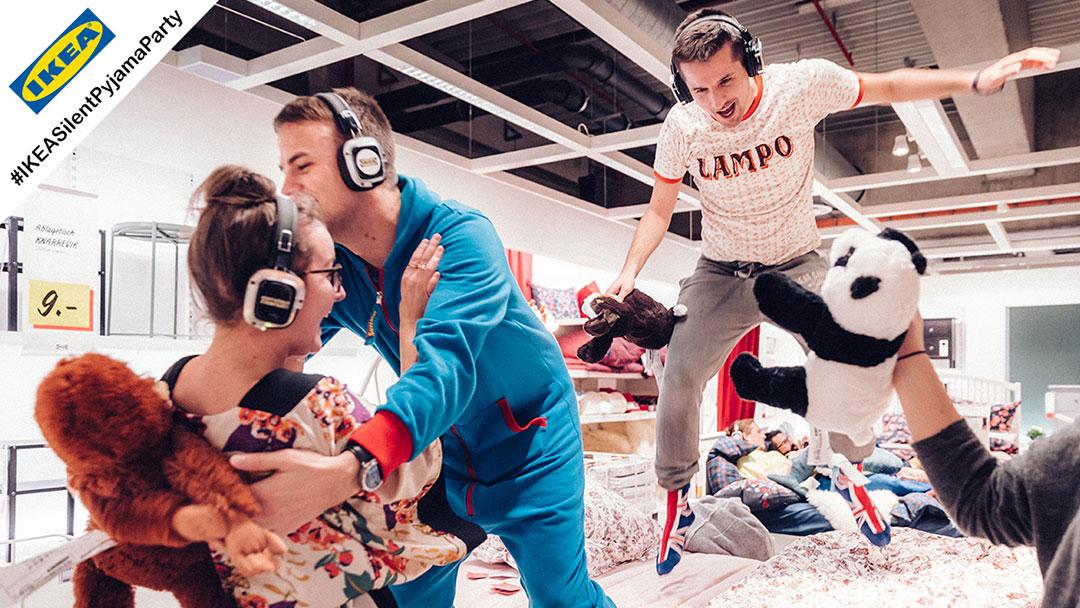Junge Menschen springen auf Bett bei Ikea Sillent Party