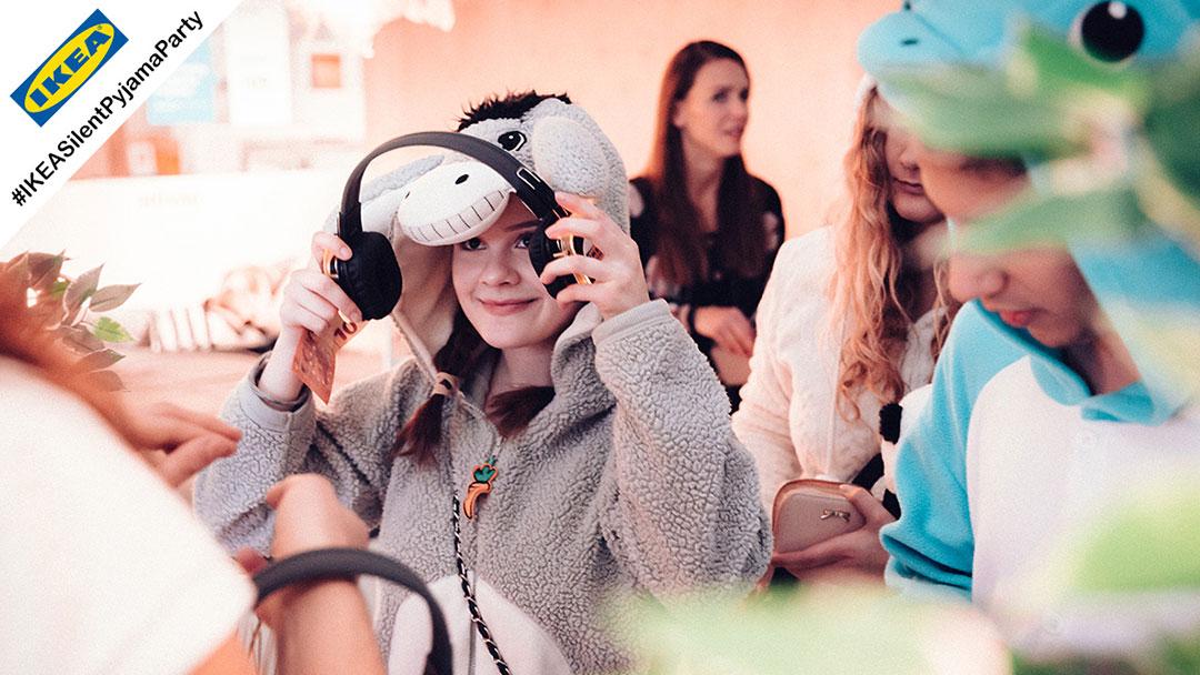 Junges Mädchen im Pyjama bei Kopfhörerparty mit Silent Disco Kopfhörer