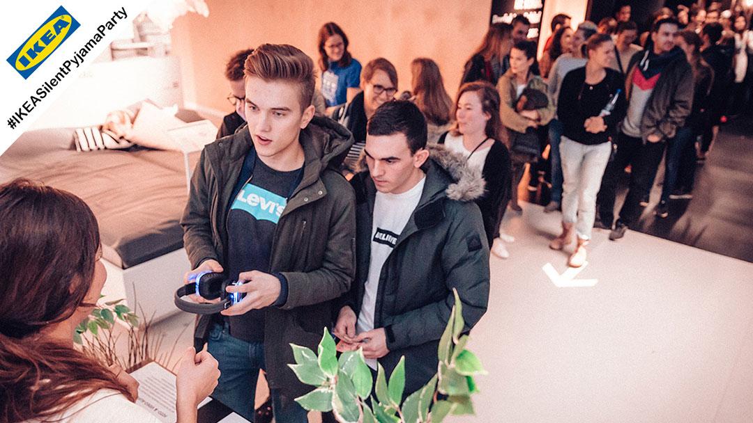 Menschen warten an der Kopfhörerausgabe bei einer Silent Disco Party bei IKEA in Ludwigsburg
