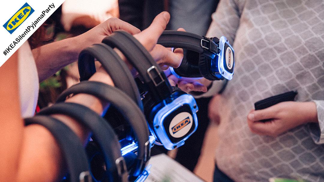 Mehrere Silent Disco Kopfhörer mit Ikea Logo leuchten blau
