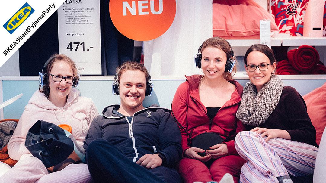 Eine Gruppe junger Mädchen auf IKEA Bett sind fröhlich während Silent Disco Party