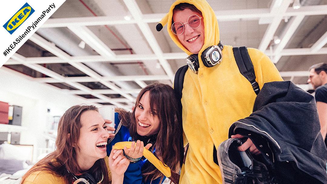 Junge Menschen im Pyjama bei IKEA Silent Disco Party haben Spass