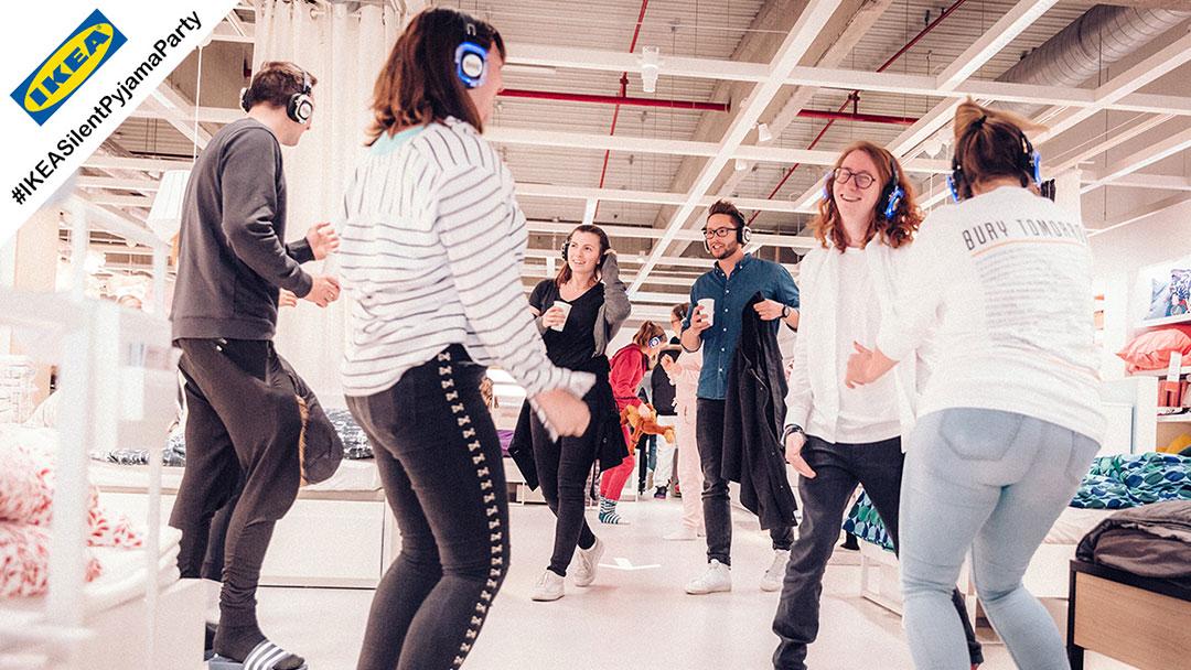 Junge Menschen im Pyjama bei IKEA Silent Disco Party haben eine gute Zeit