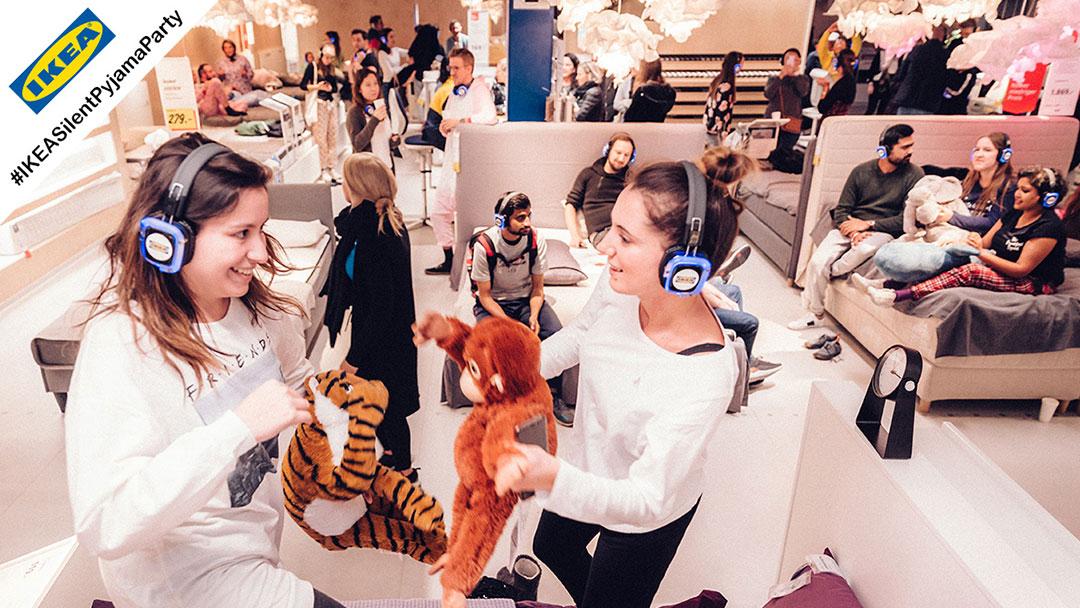 Junge Menschen im Pyjama bei IKEA Silent Disco Party tanzen auf Betten