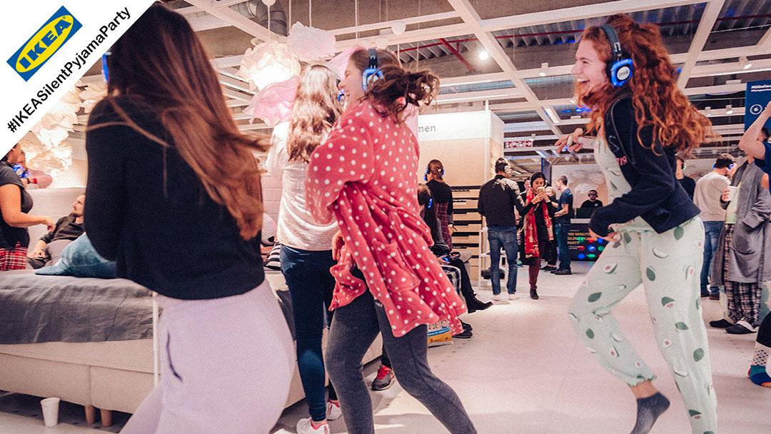 Junge Menschen im Pyjama bei IKEA Silent Disco Party tanzen und lachen