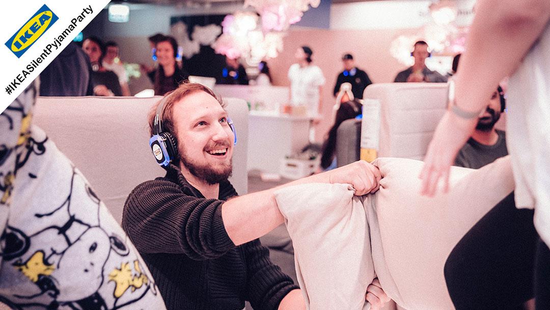 Junge Menschen im Pyjama bei IKEA Silent Disco Party machen Kissenschlacht