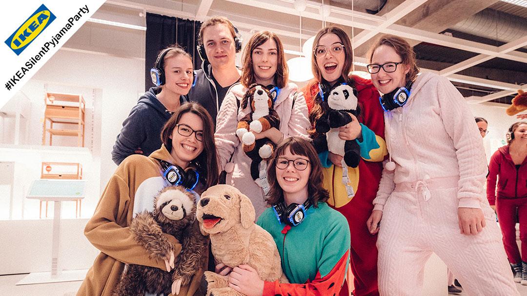 Junge Menschen im Pyjama bei IKEA Silent Disco Party mit Kuscheltieren strahlen in die Kamera