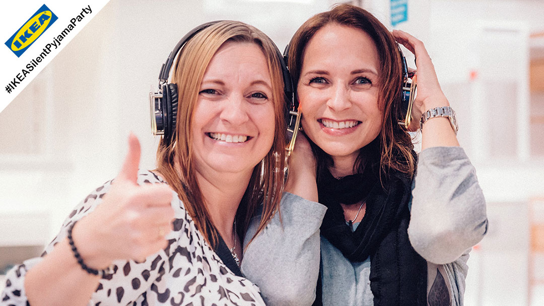 Zwei Frauen strahlen in die Kamera bei Silent Disco Party bei IKEA