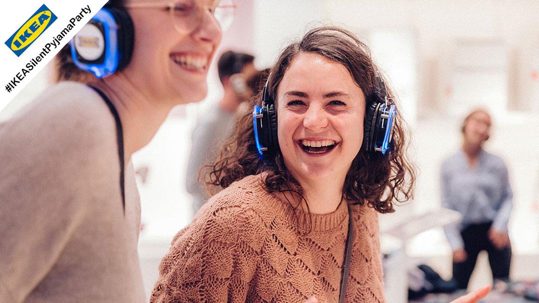 Junge Menschen im Pyjama bei IKEA Silent Disco Party lachen