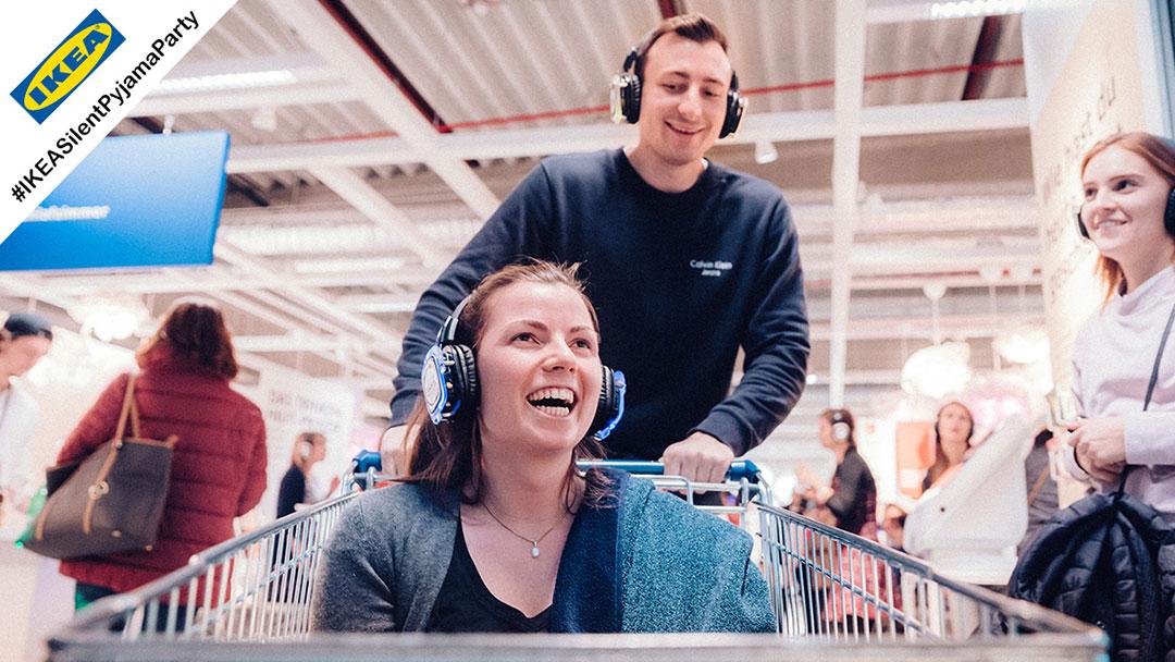 Junge Frau in Einkaufswagen hat Spass bei Silent Disco Party im Ikea