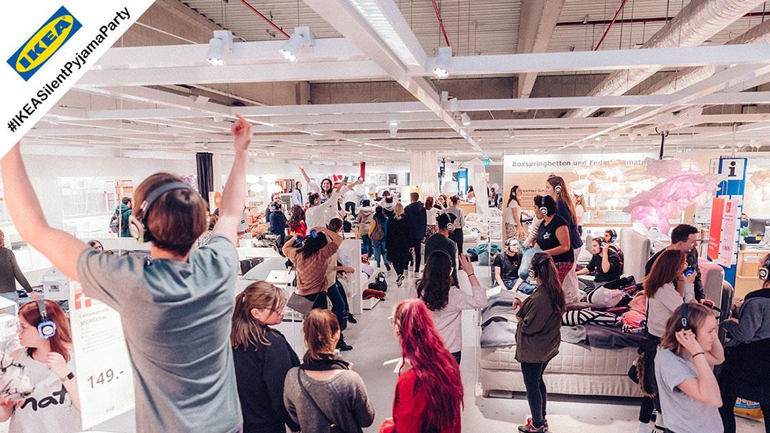 Gruppe von Menschen tanzt bei Ikea Silent Disco Party auf den Betten