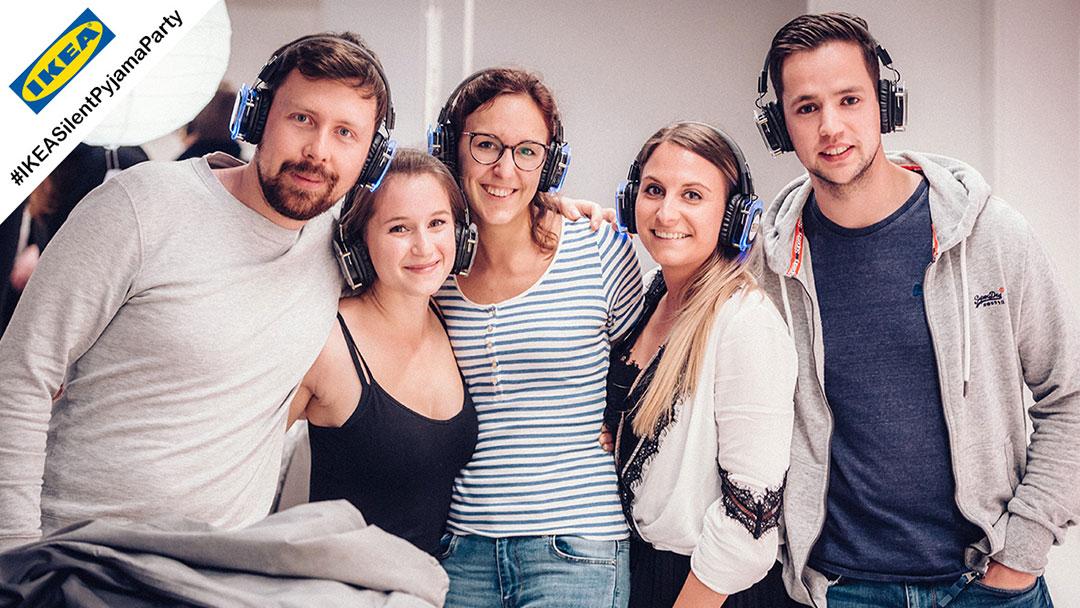 Gruppe junger Menschen lacht bei Silent Disco Ikea Party in die Kamera
