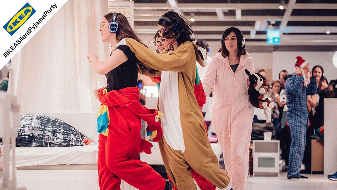 Menschen im Pyjama machen Polonäse bei Silent Disco Party bei Ikea