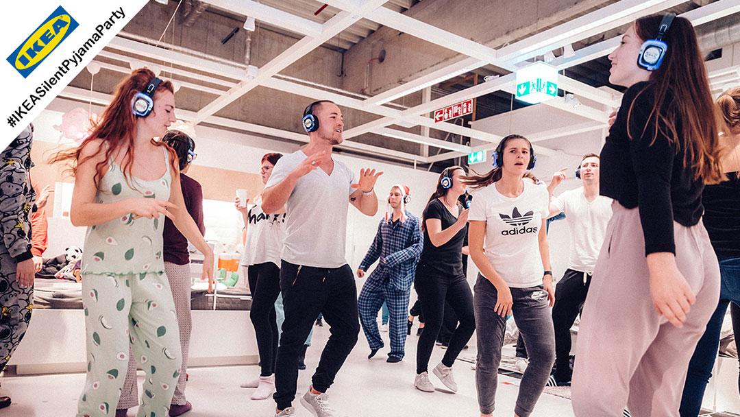 Gruppe von Menschen im Pyjama tanzen bei Ikea Silent Disco Party