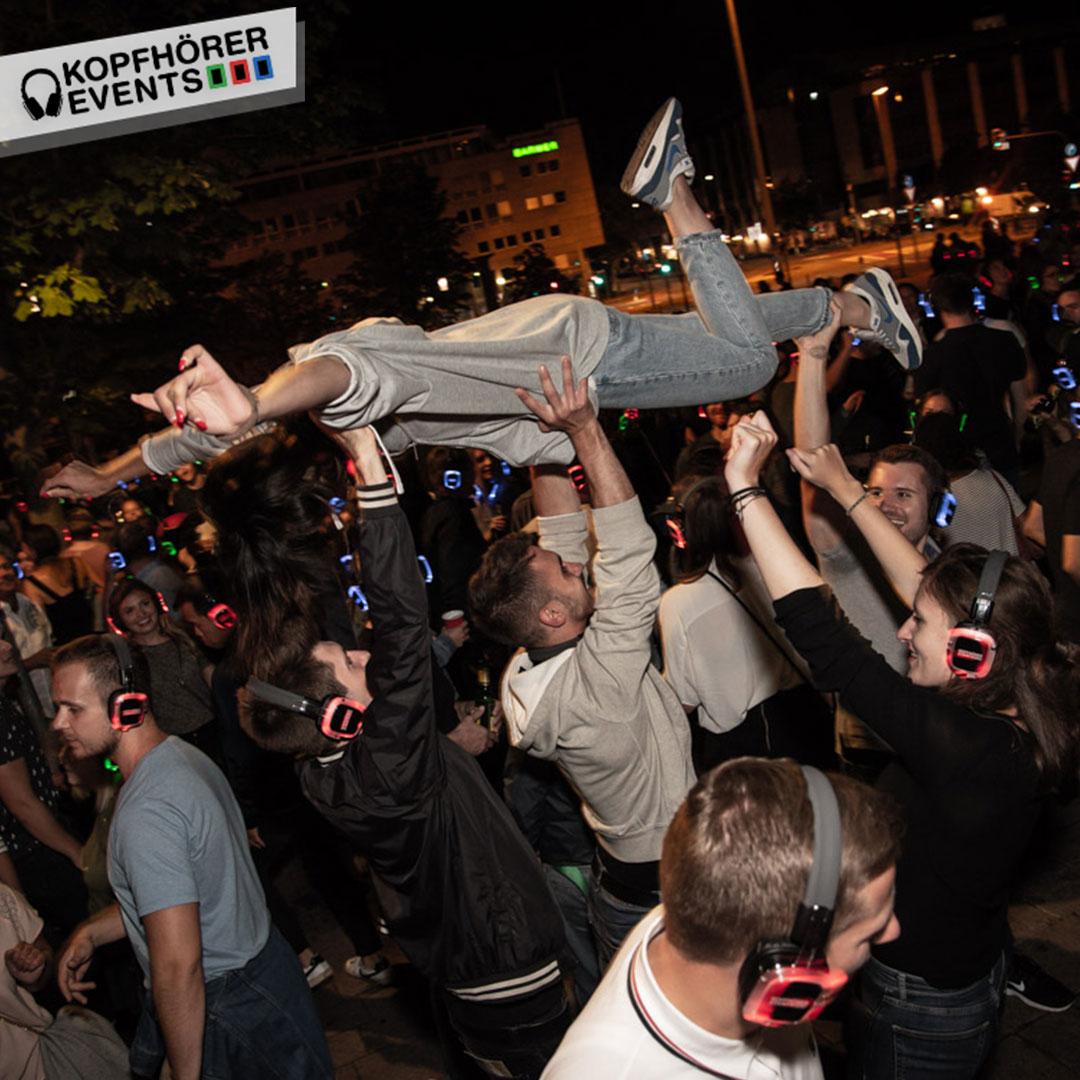 Junge Frau wird von Gruppe Menschen in die Luft gehalten wie Kate Winslet bei Titanic auf Silent Disco in Stuttgart