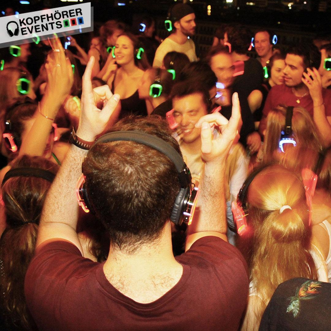 Junge Menschen bei Silent Disco Rooftop Party tanzen und werfen die Arme in die Luft