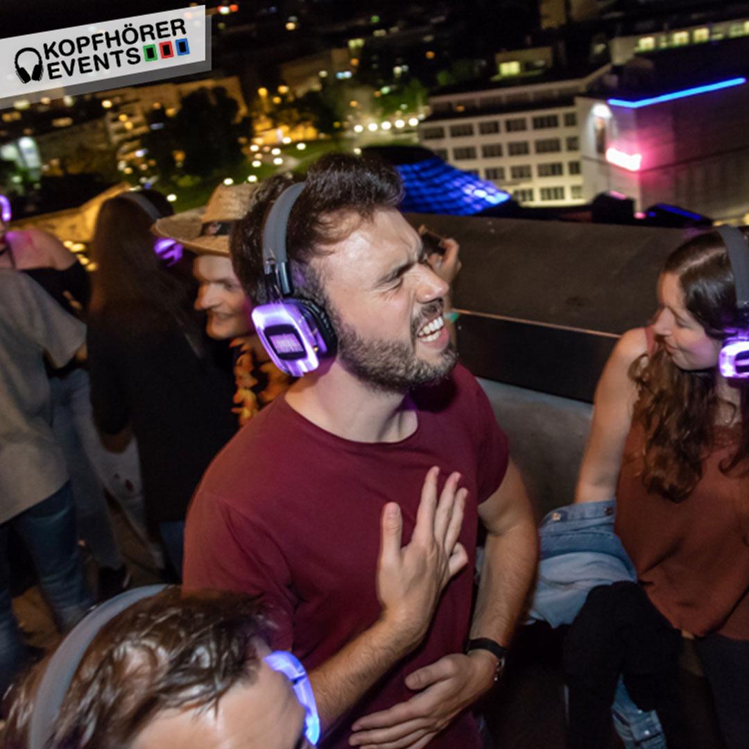 Junge Menschen bei Silent Disco Rooftop Party singen voller Inbrunst