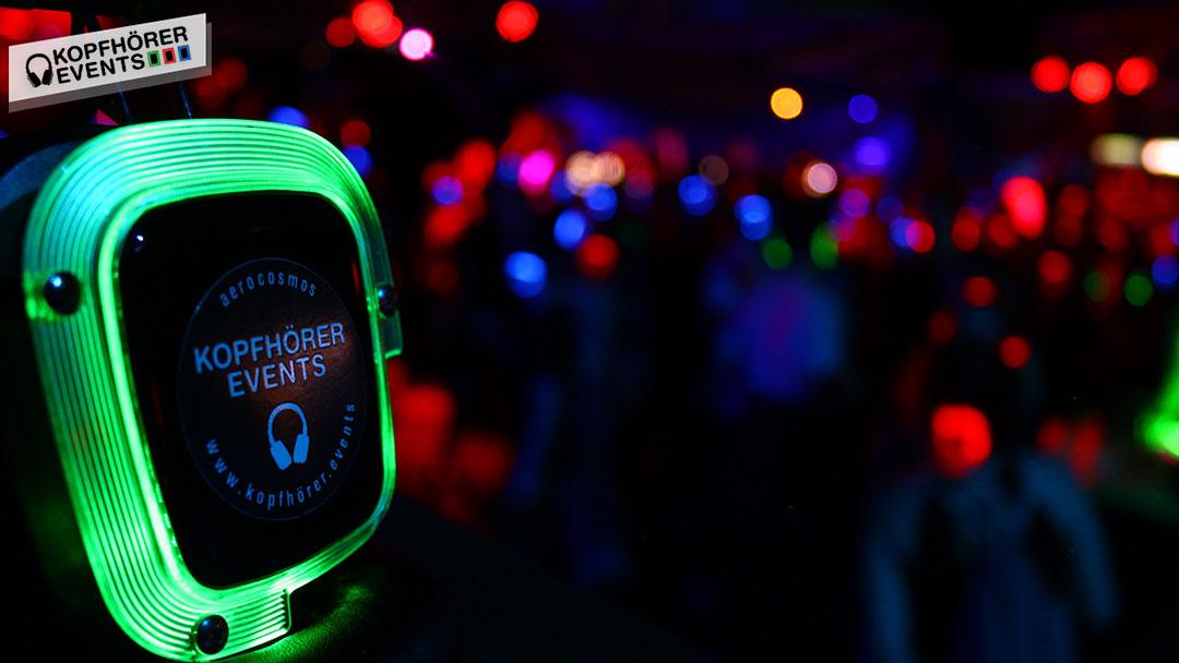 Silent Disco Kopfhörer im Vordergrund und leuchtende Kopfhörer auf der Tanzfläche
