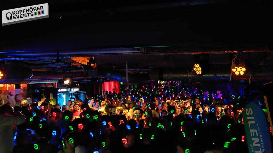 Silent Disco Party Tanzfläche mit vielen bunten Kopfhörern die leuchten