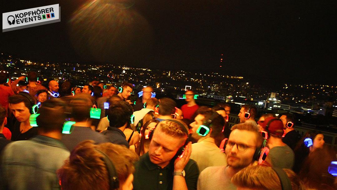 Menschen bei Silent Disco Rooftop Party mit Skyline von Stuttgart im Hintergrund