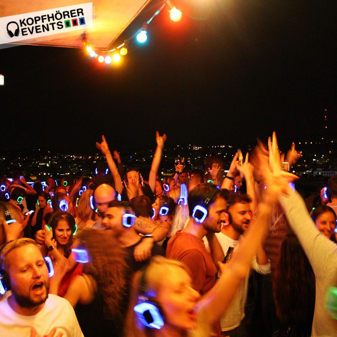 Junge Menschen bei Silent Disco Rooftop Party feiern ausgelassen