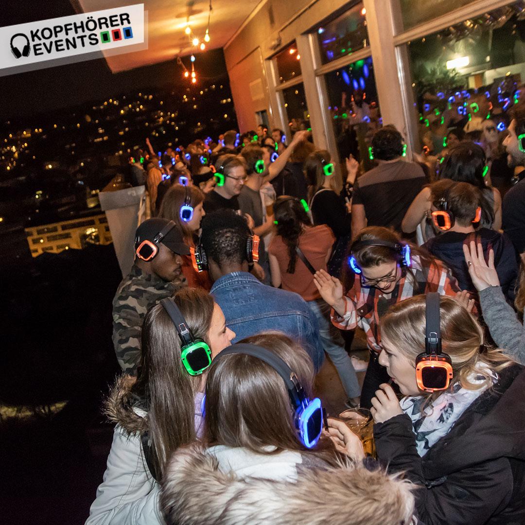 Junge Menschen bei Silent Disco Rooftop Party sind fröhlich und tanzen