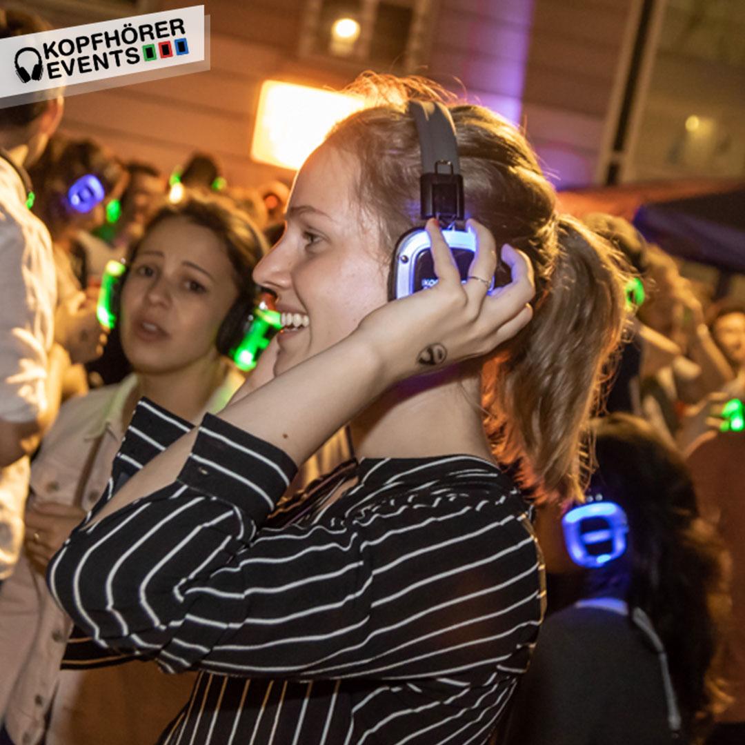 Junge Frau lacht während Silent Disco in Stuttgart