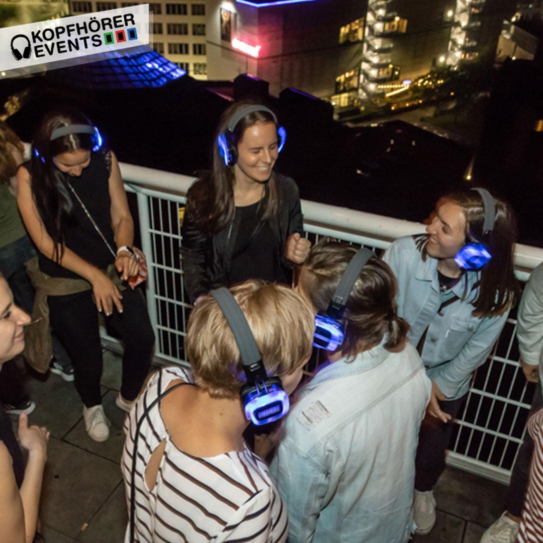Junge Menschen bei Silent Disco Rooftop Party sind ausgelassen lachen und haben Spaß
