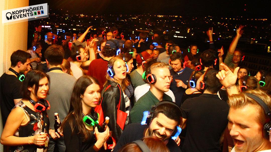 Junge Menschen bei Silent Disco Rooftop Party tanzen und lachen