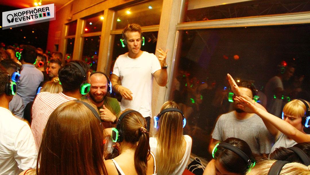 Junge Menschen bei Silent Disco Rooftop Party tanzen auf den Tischen