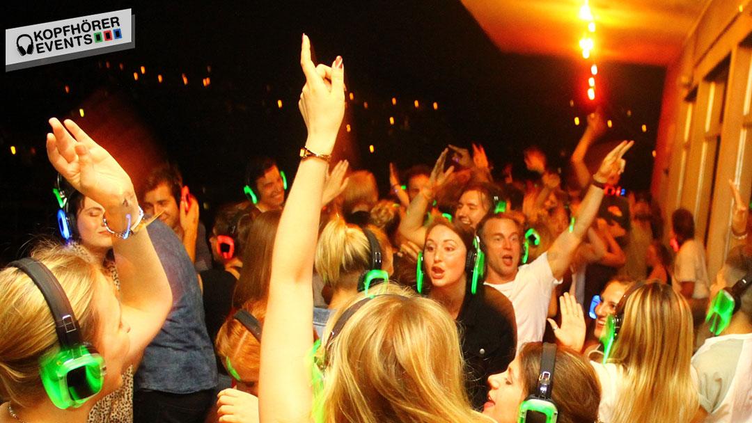 Junge Menschen bei Silent Disco Rooftop Party tanzen mit Armen in der Luft