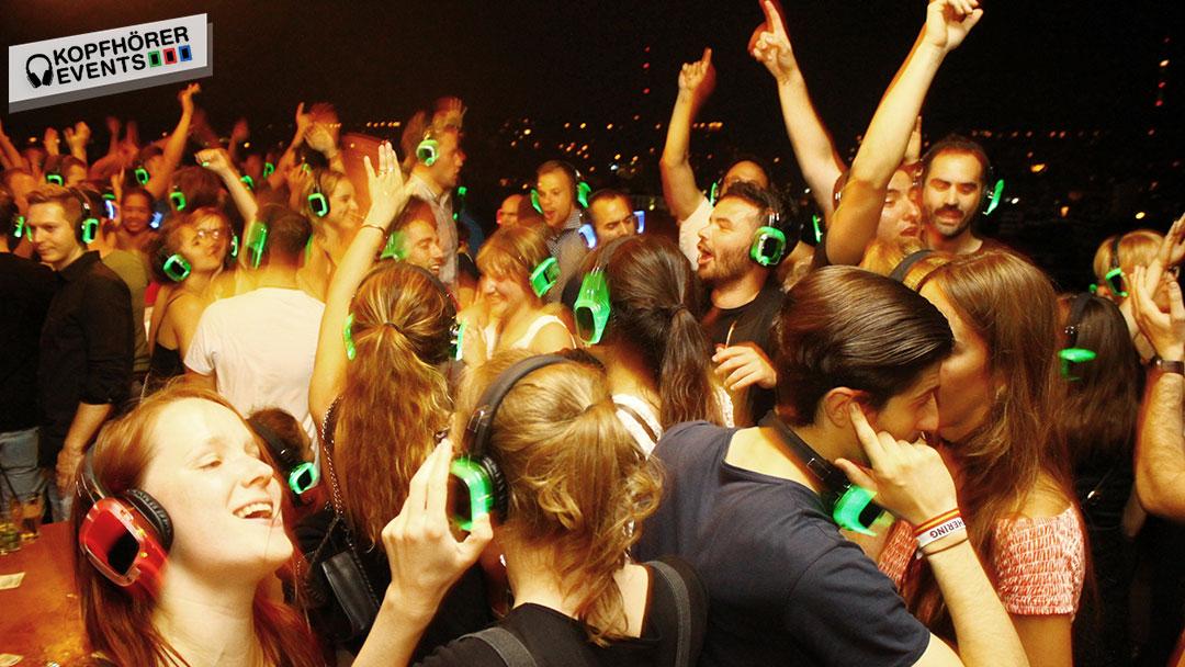 Junge Menschen bei Silent Disco Rooftop Party singen und tanzen