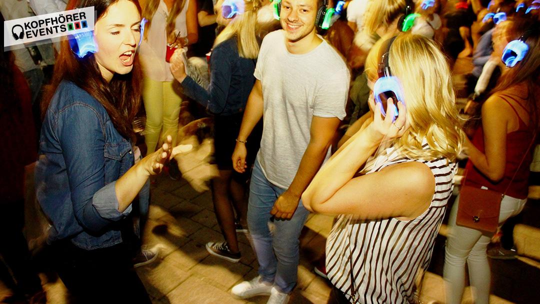 Junger Mann und junge Frau tanzen und lachen bei Silent Disco Stuttgart